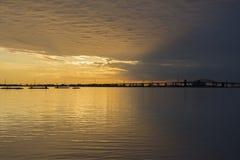 O nascer do sol bonito e o céu tormentoso sobre o lago tranquilo molham, brid Fotografia de Stock