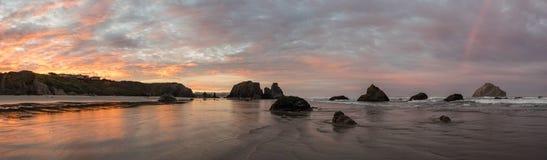 O nascer do sol e o arco-íris no oceano encalham com penhascos Imagens de Stock Royalty Free