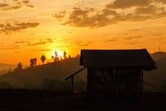 O nascer do sol e a uma cabana Imagem de Stock Royalty Free