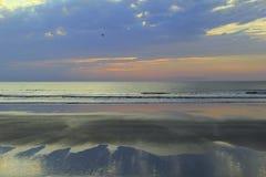 O nascer do sol impressionante de azul, de cor-de-rosa e roxos, sobre o oceano molha Imagens de Stock Royalty Free