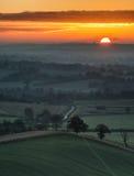 O nascer do sol impressionante sobre a névoa mergulha na paisagem do campo Fotografia de Stock Royalty Free