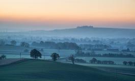 O nascer do sol impressionante sobre a névoa mergulha na paisagem do campo Foto de Stock