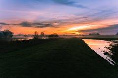 O nascer do sol inflama o céu no banco de rio Fotografia de Stock