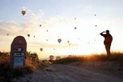 O nascer do sol nas montanhas com muitos balões quentes do ar no céu Imagens de Stock Royalty Free