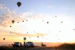O nascer do sol nas montanhas com muitos balões quentes do ar no céu Fotografia de Stock