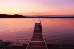 O nascer do sol por um lago que inspira relaxa e tranquilidade Fotos de Stock