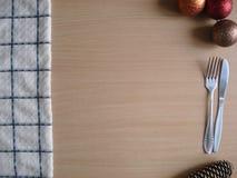 O Natal brinca com cutelaria e uma toalha na mesa de cozinha Fotos de Stock