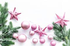 O Natal brinca o teste padrão As estrelas e as bolas cor-de-rosa perto do pinho ramificam no copyspace branco da opinião superior Imagens de Stock Royalty Free