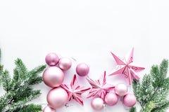 O Natal brinca o teste padrão As estrelas e as bolas cor-de-rosa perto do pinho ramificam no copyspace branco da opinião superior Foto de Stock