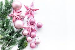 O Natal brinca o teste padrão As estrelas e as bolas cor-de-rosa perto do pinho ramificam no copyspace branco da opinião superior Foto de Stock Royalty Free