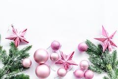O Natal brinca o teste padrão As estrelas e as bolas cor-de-rosa perto do pinho ramificam no copyspace branco da opinião superior Imagem de Stock Royalty Free