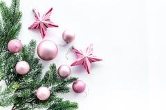 O Natal brinca o teste padrão As estrelas e as bolas cor-de-rosa perto do pinho ramificam no copyspace branco da opinião superior Fotografia de Stock Royalty Free