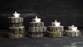 O Natal candles o burning, decoração com os logs de madeira que descansam o imagem de stock