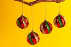 O Natal colorido redondo ornaments a suspensão do ramo dourado contra o fundo amarelo fotografia de stock royalty free