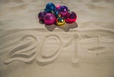 O Natal coloriu bolas encontra-se na praia, ao lado da areia, a data é escrito Foto de Stock Royalty Free