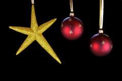 O Natal de suspensão star e dois ornamento vermelhos da esfera. Fotografia de Stock
