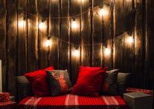 O Natal decorou o lugar em uma sala com a parede, as lâmpadas, os descansos dos veados vermelhos e a manta de madeira velhos Foto de Stock Royalty Free