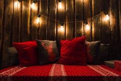 O Natal decorou o lugar em uma sala com a parede, as lâmpadas, os descansos dos veados vermelhos e a manta de madeira velhos Fotos de Stock Royalty Free