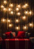 O Natal decorou o lugar em uma sala com a parede, as lâmpadas, os descansos dos veados vermelhos e a manta de madeira velhos Fotografia de Stock