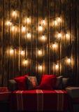 O Natal decorou o lugar em uma sala com a parede, as lâmpadas, os descansos dos veados vermelhos e a manta de madeira velhos Imagem de Stock