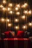 O Natal decorou o lugar em uma sala com a parede, as lâmpadas, os descansos dos veados vermelhos e a manta de madeira velhos Imagens de Stock