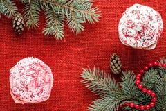 O Natal decorou queques na opinião superior do fundo vermelho de serapilheira Fotografia de Stock Royalty Free