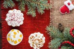 O Natal decorou queques na opinião superior do fundo vermelho de serapilheira Imagens de Stock Royalty Free