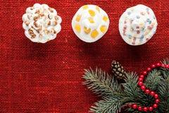 O Natal decorou queques na opinião superior do fundo vermelho de serapilheira Imagens de Stock