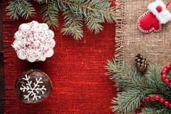 O Natal decorou queques na opinião superior do fundo vermelho de serapilheira Fotos de Stock Royalty Free