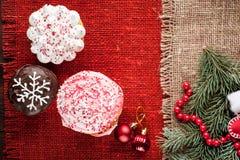 O Natal decorou queques na opinião superior do fundo vermelho de serapilheira Imagem de Stock Royalty Free