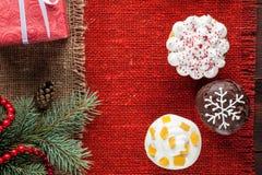 O Natal decorou queques na opinião superior do fundo vermelho de serapilheira Imagem de Stock