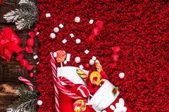 O Natal golpeia completamente dos doces e dos doces no fundo felpudo vermelho Configuração lisa Copie o espaço Foto de Stock Royalty Free
