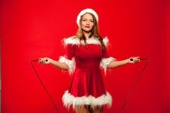 O Natal, x-mas, inverno, conceito da felicidade - ostente, atividade Mulher bonito com corda de salto no chapéu do ajudante de Sa foto de stock