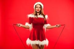 O Natal, x-mas, inverno, conceito da felicidade - ostente, atividade Mulher bonito com corda de salto no chapéu do ajudante de Sa imagens de stock royalty free