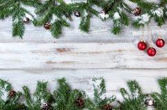 O Natal nevado ramifica com os ornamento vermelhos na madeira branca rústica imagem de stock royalty free
