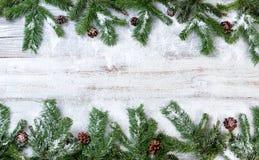O Natal nevado ramifica no fundo de madeira branco rústico fotografia de stock