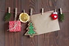 O Natal objeta em uma corda em clothespegs no fundo de madeira Foto de Stock Royalty Free