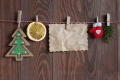 O Natal objeta em uma corda em clothespegs no fundo de madeira Fotografia de Stock Royalty Free