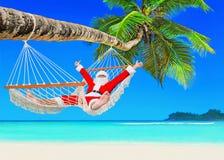 O Natal positivo Santa Claus relaxa na rede em Palm Beach fotos de stock royalty free