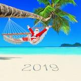 O Natal positivo Santa Claus relaxa na rede em Palm Beach e no subtítulo do ano novo feliz 2019 na areia branca fotografia de stock