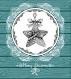 O Natal protagoniza no círculo no estilo da Zen-garatuja com laço no fundo de madeira azul Foto de Stock Royalty Free
