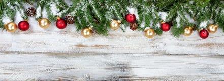 O Natal ramifica com os ornamento dourados e vermelhos com neve no ru Foto de Stock