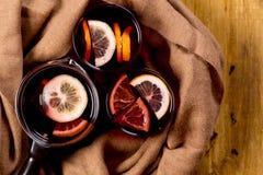 O Natal sazonal e dos feriados do conceito ferventou com especiarias o vinho com fatias alaranjadas bonitas dentro do vidro, cobe fotografia de stock