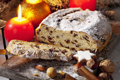 O Natal stollen com as porcas do galho do pinho das varas de canela das estrelas da canela das velas na placa de madeira Fotos de Stock Royalty Free