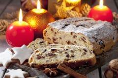 O Natal stollen com as porcas do galho do pinho das varas de canela das estrelas da canela das velas na placa de madeira Fotografia de Stock Royalty Free