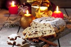 O Natal stollen na placa de madeira com presente do galho do pinho das varas de canela das estrelas da canela dos bulbos do Natal Fotos de Stock Royalty Free