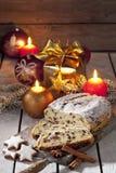 O Natal stollen na placa de madeira com presente do galho do pinho das varas de canela das estrelas da canela dos bulbos do Natal Imagens de Stock