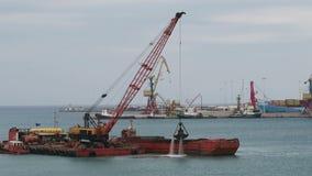 O navio da draga está agarrando a areia do botão do porto em Iraklion e está carregando o navio Crete, Greece Nuvens do clima de  filme