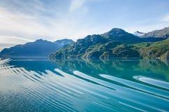 O navio de cruzeiros cria ondinhas através das águas calmas do mar Fotos de Stock Royalty Free