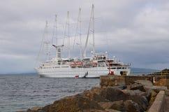 O navio de cruzeiros da ressaca do vento offloads passageiros Foto de Stock